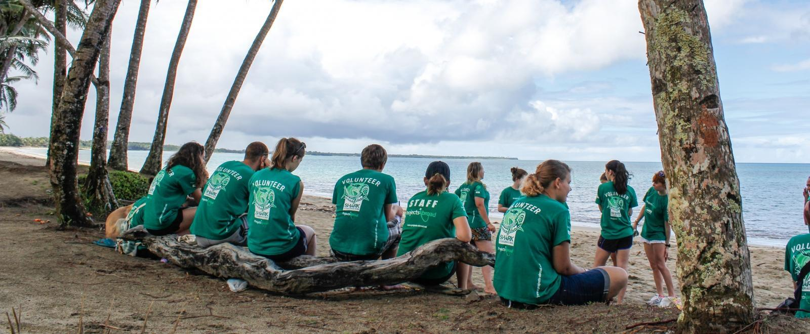 Projects Abroad volunteers in Fiji take a break after a beach clean-up.